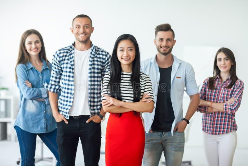Grupo de hombres de negocios sonrientes con el líder asiático de la empresaria fotos de archivo libres de regalías