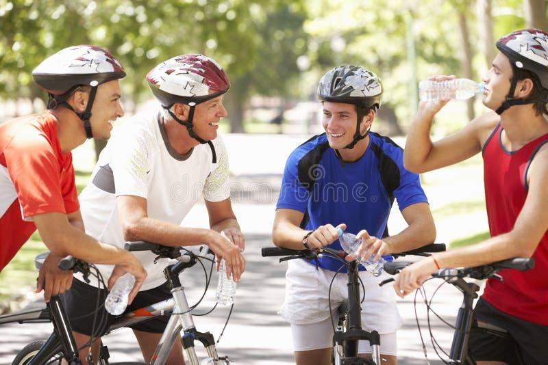 Grupo de hombres que descansan durante paseo del ciclo a través de parque foto de archivo libre de regalías