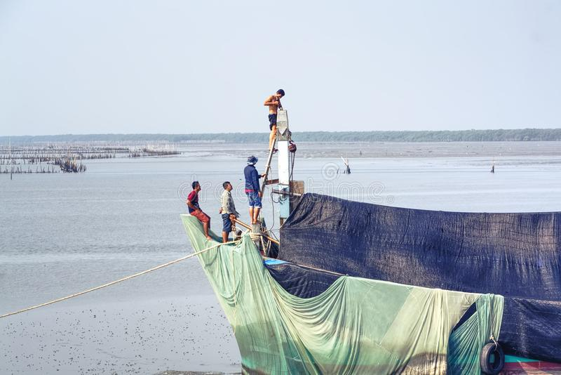 Grupo de hombres que reparan al pescador Ship fotografía de archivo libre de regalías