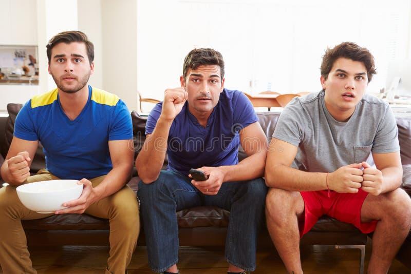 Grupo de hombres que se sientan en Sofa Watching Sport Together imagen de archivo libre de regalías