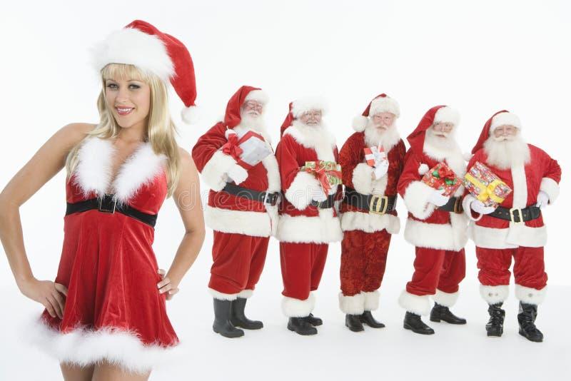 Grupo de hombres vestidos como Santa Claus Standing With Mrs. Claus In Foreground fotografía de archivo