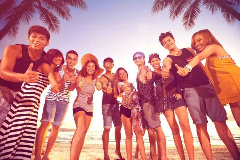 Grupo de hombres y de mujeres sonrientes que muestran los pulgares para arriba en la playa fotos de archivo libres de regalías