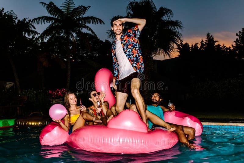 Grupo de hombres y de mujeres que van de fiesta en la piscina foto de archivo libre de regalías