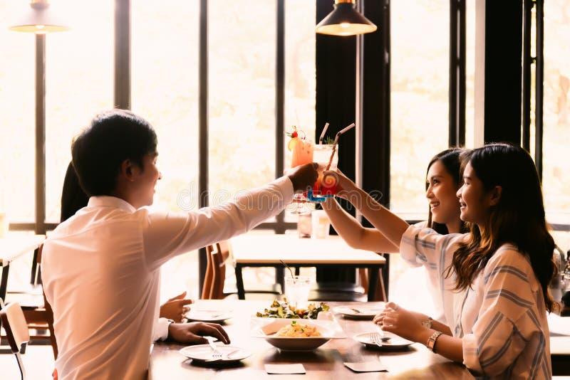 Grupo de homem novo asiático e de mulheres felizes e sorrindo que mantêm um cocktail alcoólico para brindar no restaurante contra fotografia de stock royalty free