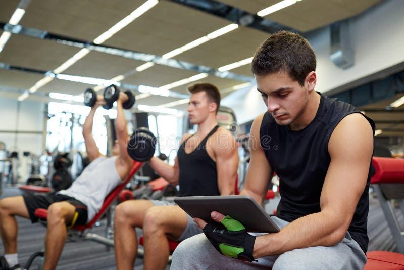 Grupo de homens com PC da tabuleta e de pesos no gym foto de stock royalty free
