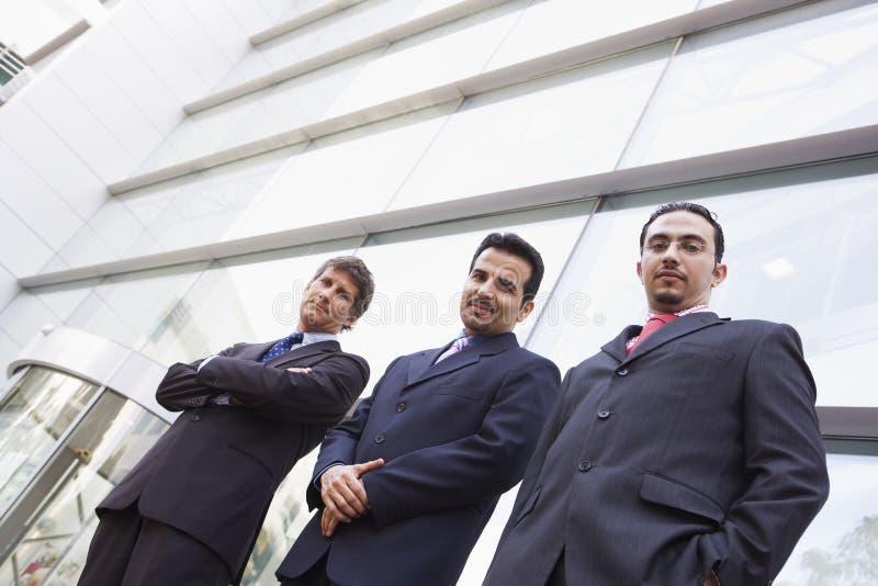 Grupo de homens de negócios fora do prédio de escritórios imagem de stock