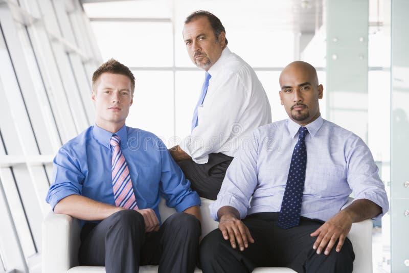 Grupo de homens de negócios que sentam-se na entrada imagens de stock
