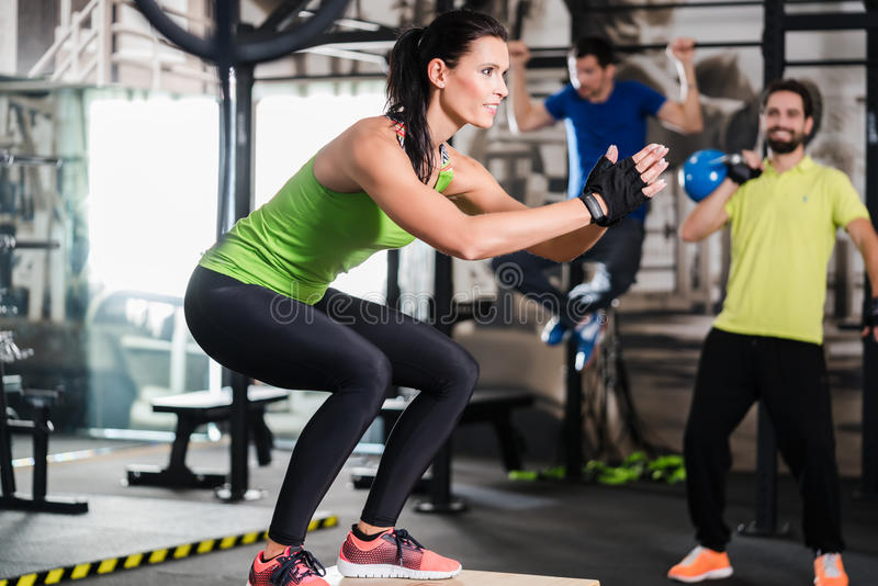 Grupo de homens e de mulher no gym funcional do treinamento imagem de stock