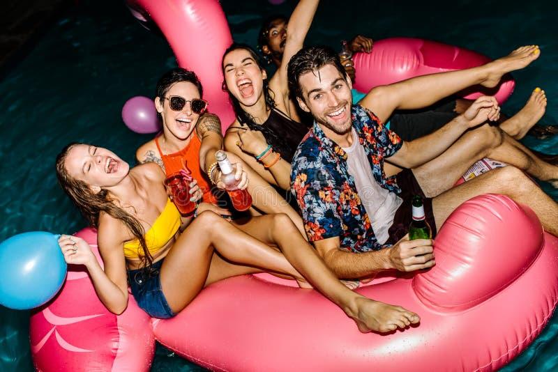 Grupo de homens e de mulheres que apreciam na festa na piscina imagens de stock royalty free