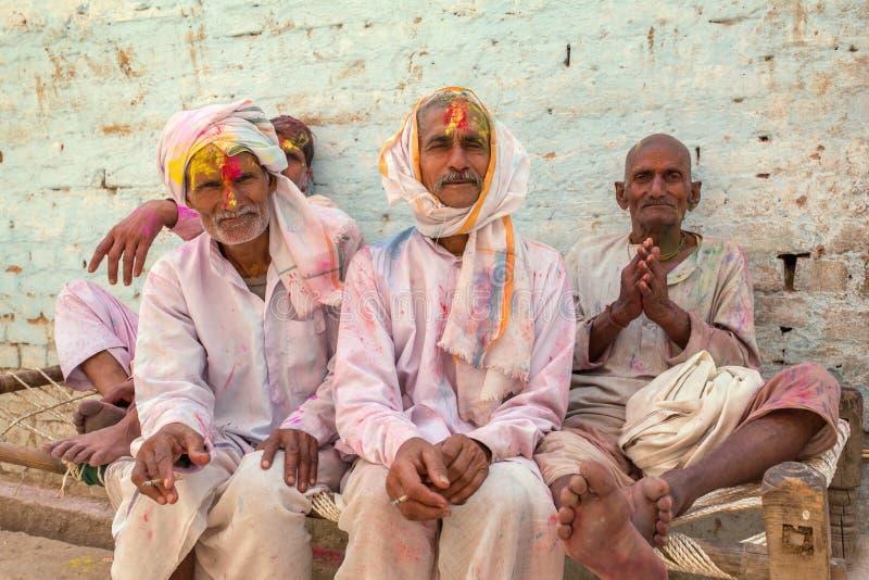Grupo de homens indianos não identificados coloridos com cores durante a celebração de Holi em Nandgaon fotos de stock royalty free