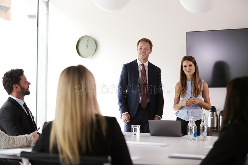 Grupo de homens de negócios novos e de mulheres de negócios que encontram-se em torno da tabela no dia graduado da avaliação do r fotos de stock royalty free