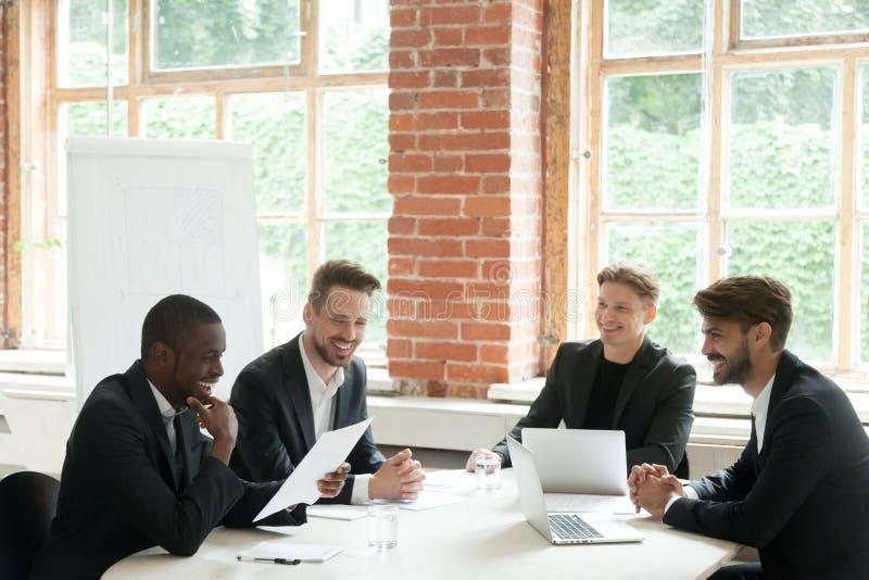 Grupo de homens de negócios de sorriso alegres durante a reunião de instrução imagens de stock royalty free