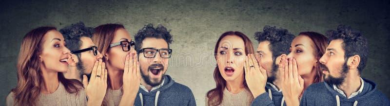 Grupo de homens novos e de mulheres que sussurram-se na orelha fotos de stock royalty free