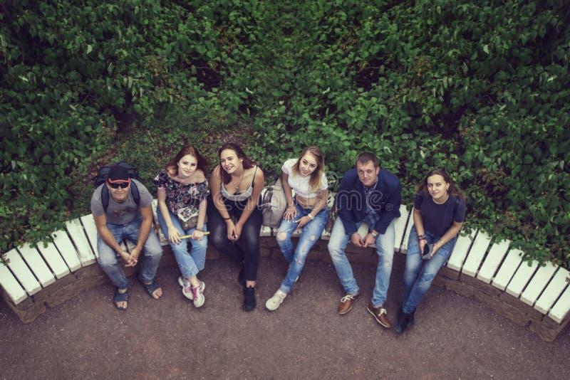 Grupo de homens novos felizes e de mulheres que olham acima de assento em um semi- imagens de stock