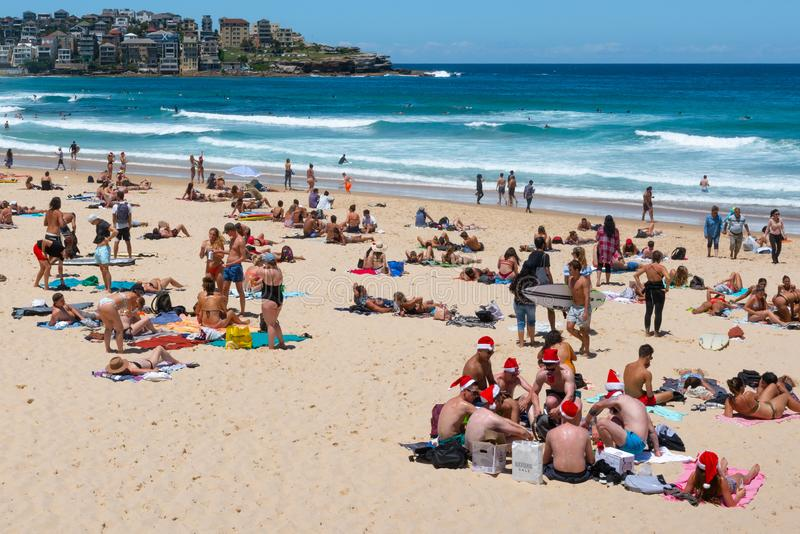 Grupo de homens novos que vestem chapéus de Santa na Noite de Natal na praia Sydney Australia de Bondi imagem de stock