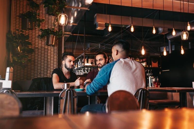 Grupo de homens novos de raça misturada que falam na barra da sala de estar Amigos multirraciais que penduram para fora e que têm fotografia de stock