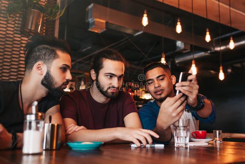 Grupo de homens novos de raça misturada que falam na barra da sala de estar Amigos multirraciais que têm o divertimento no café I foto de stock