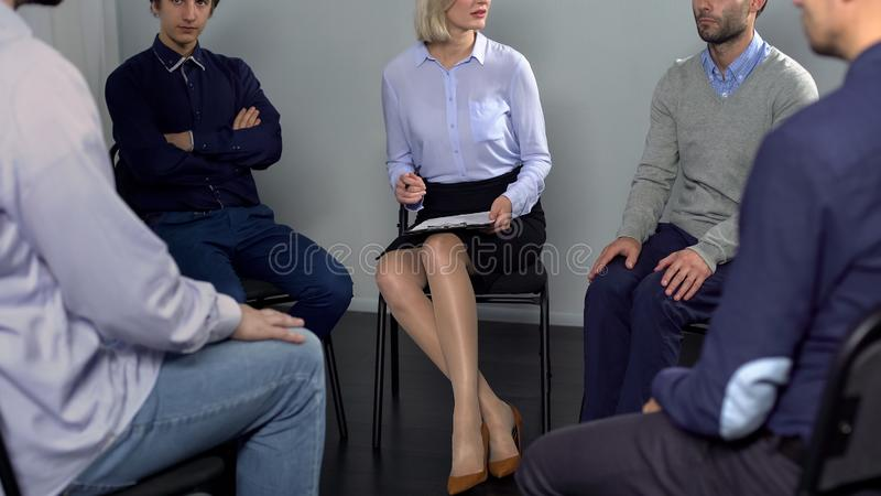 Grupo de homens que discutem o conflito de trabalho com o colega na reunião da psicoterapia imagem de stock royalty free