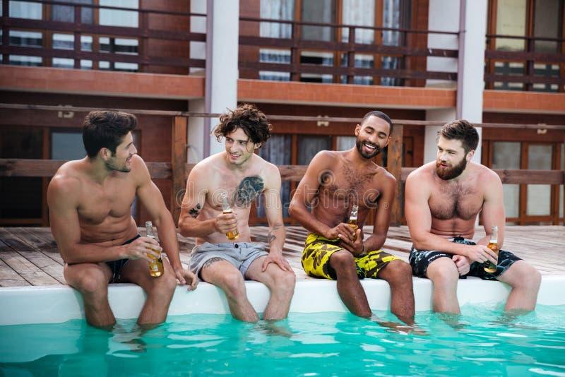Grupo de homens que sentam e que bebem a cerveja perto da piscina fotos de stock