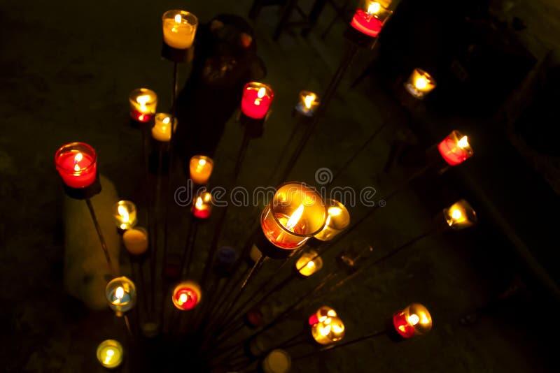 Grupo de iluminar velas na obscuridade foto de stock