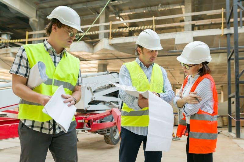 Grupo de ingenieros, constructores, arquitectos en el solar Concepto de la construcción, del desarrollo, del trabajo en equipo y  imágenes de archivo libres de regalías