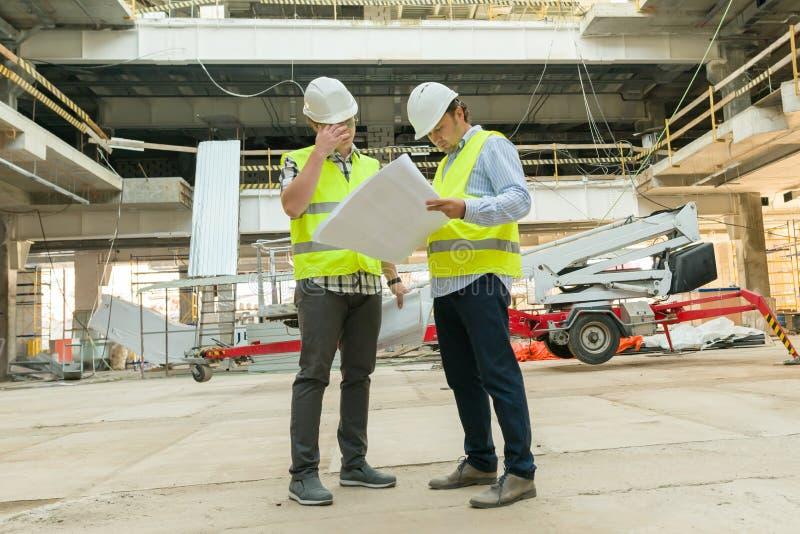 Grupo de ingenieros, constructores, arquitectos en el solar Concepto de la construcción, del desarrollo, del trabajo en equipo y  imagenes de archivo