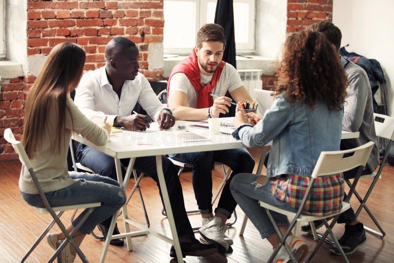 Grupo de intercambio de ideas creativo del trabajador cinco junto en la oficina, nuevo estilo del espacio de trabajo, escena feli imagen de archivo libre de regalías