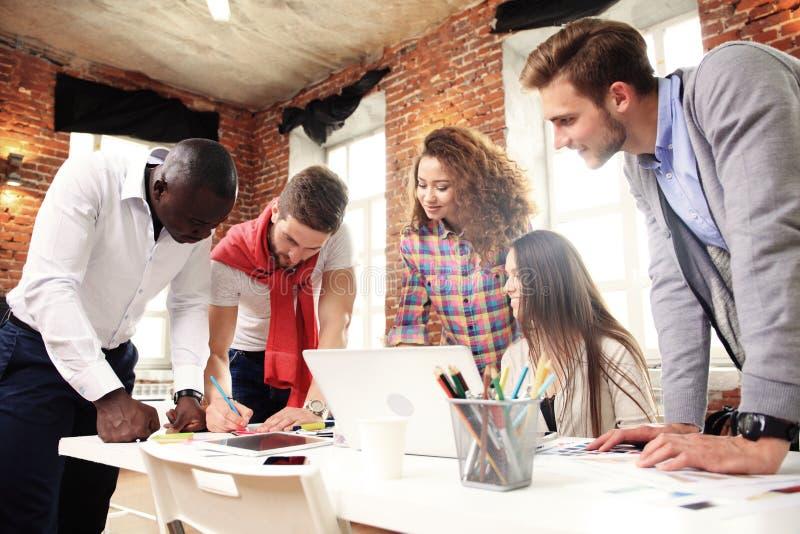 Grupo de intercambio de ideas creativo del trabajador cinco junto en la oficina, nuevo estilo del espacio de trabajo, escena feli fotos de archivo