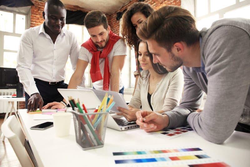 Grupo de intercambio de ideas creativo del trabajador cinco junto en la oficina, nuevo estilo del espacio de trabajo, escena feli imágenes de archivo libres de regalías