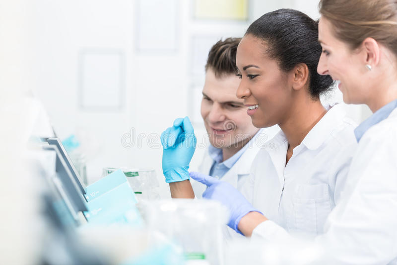 Grupo de investigadores durante trabajo sobre los dispositivos en laboratorio foto de archivo