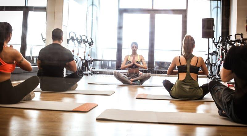 Grupo de ioga do exercício dos jovens junto fotos de stock