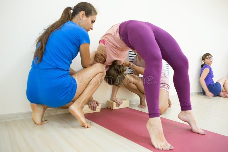 Grupo de ioga praticando dos povos do positivel no gym imagens de stock royalty free