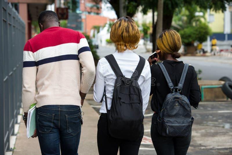 Grupo de jóvenes con mochilas caminando por la ciudad fotos de archivo libres de regalías