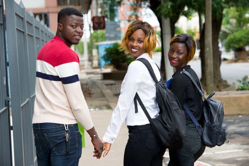 Grupo de jóvenes con mochilas caminando por la ciudad fotografía de archivo