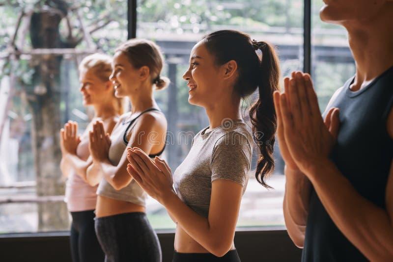 Grupo de jóvenes practicando yoga En la posición de oración en el gimnasio, Concepto de relajación y meditación fotos de archivo libres de regalías