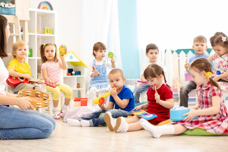 Grupo de jogo de crianças do jardim de infância com brinquedos musicais Educação musical adiantada na guarda fotografia de stock royalty free