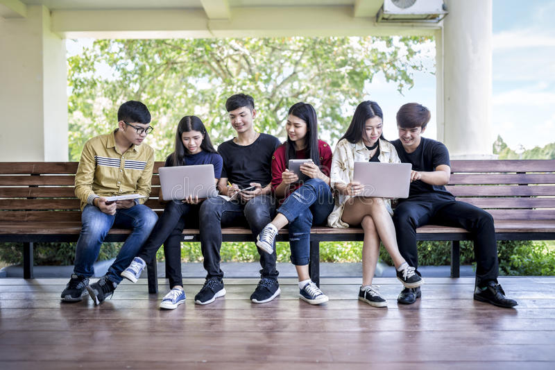 Grupo de jovens asiáticos que estudam na universidade que senta-se no ch imagens de stock