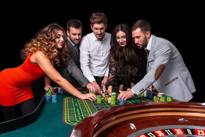 Grupo de jovens atrás da tabela da roleta em um casino fotografia de stock royalty free