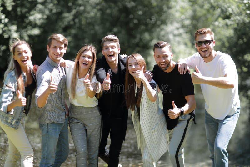 Grupo de jovens bem sucedidos que mostram o polegar acima fotografia de stock royalty free