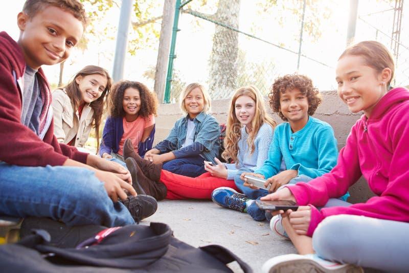Grupo de jovens crianças que penduram para fora no campo de jogos foto de stock royalty free