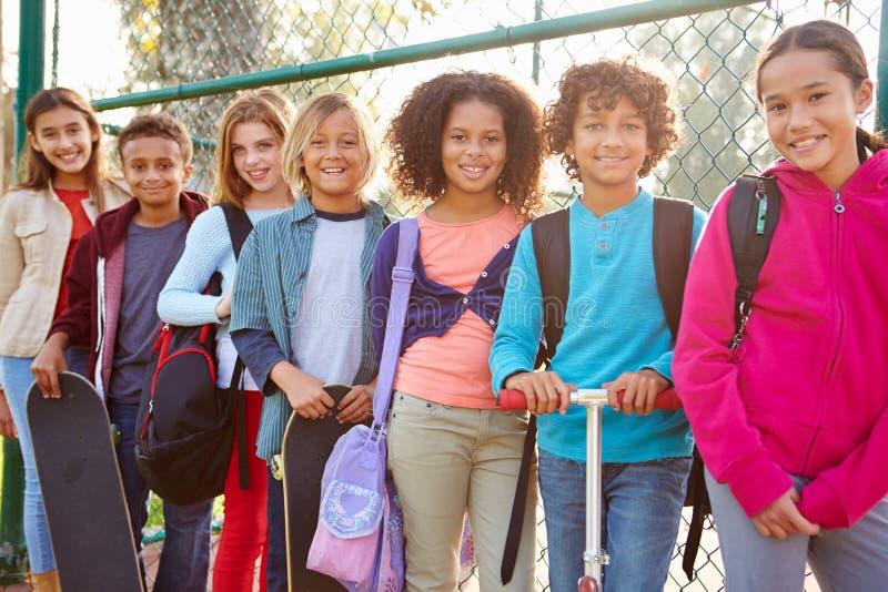 Grupo de jovens crianças que penduram para fora no campo de jogos fotos de stock royalty free
