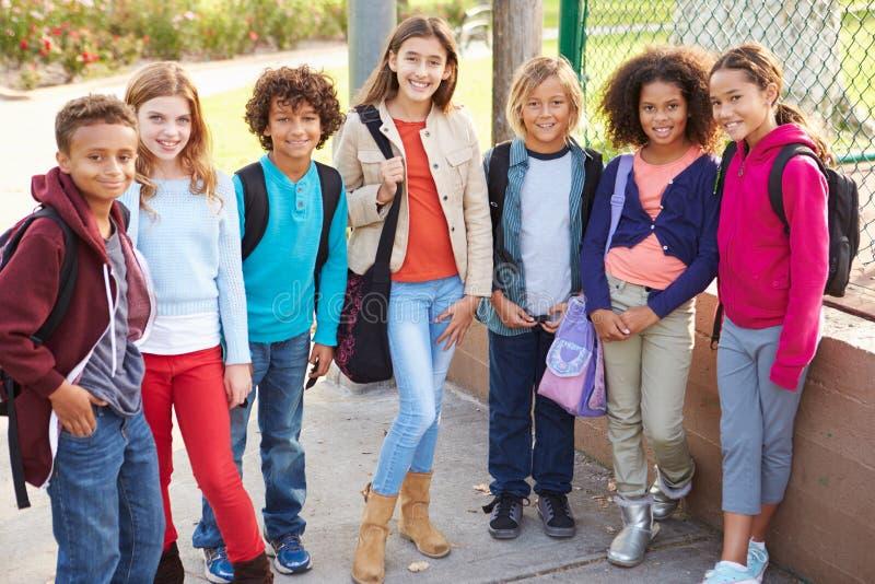Grupo de jovens crianças que penduram para fora no campo de jogos fotografia de stock royalty free