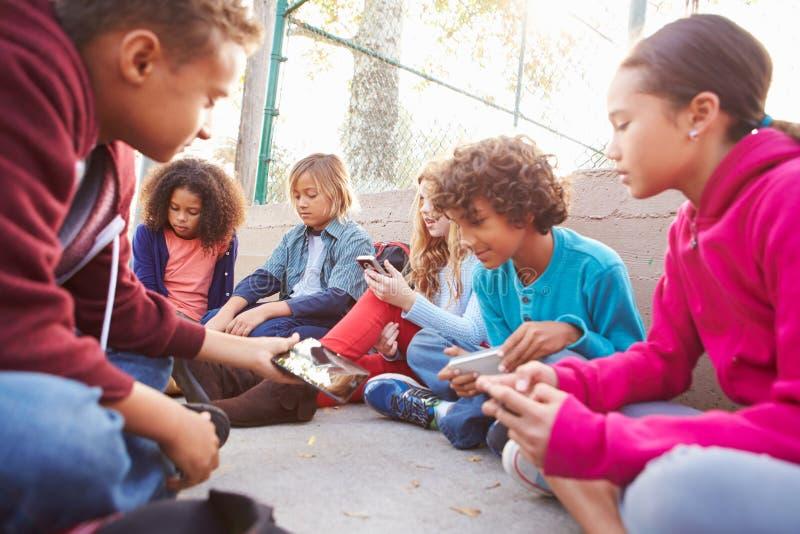 Grupo de jovens crianças que penduram para fora no campo de jogos fotografia de stock