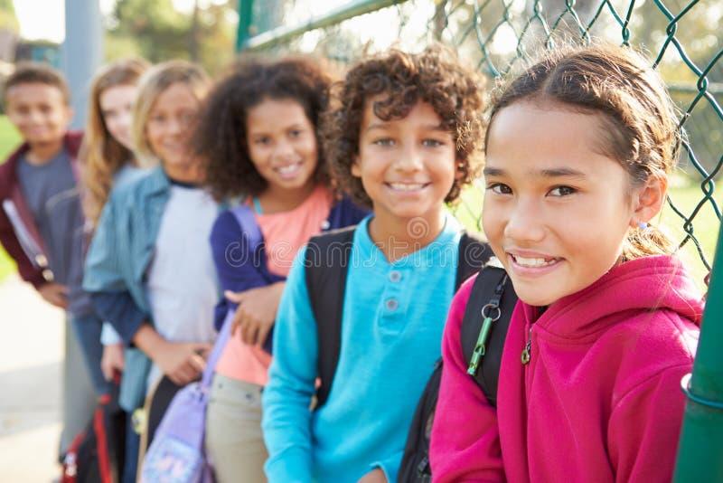 Grupo de jovens crianças que penduram para fora no campo de jogos imagens de stock royalty free