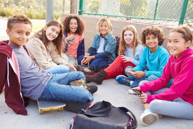 Grupo de jovens crianças que penduram para fora no campo de jogos imagem de stock