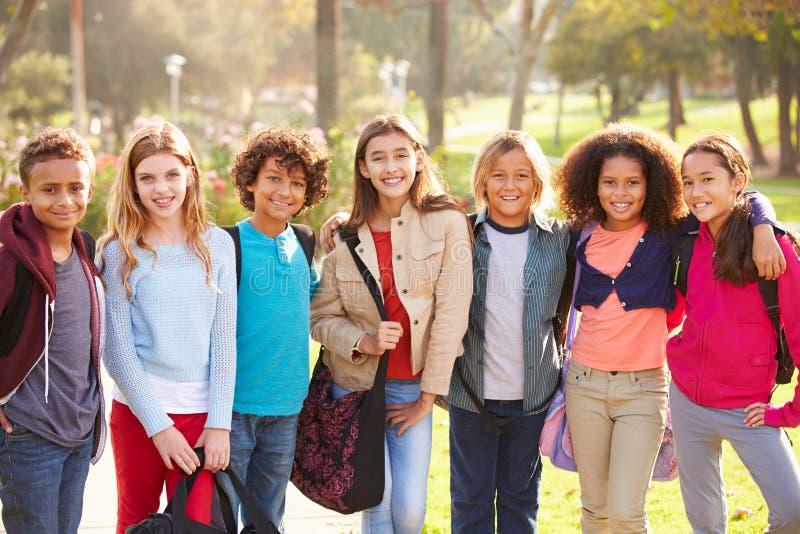 Grupo de jovens crianças que penduram para fora no parque imagens de stock