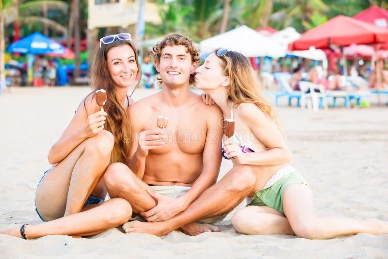 Grupo de jovens felizes que comem o gelado sobre fotos de stock