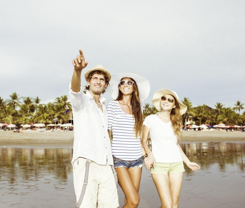 Grupo de jovens felizes que ficam na praia foto de stock royalty free