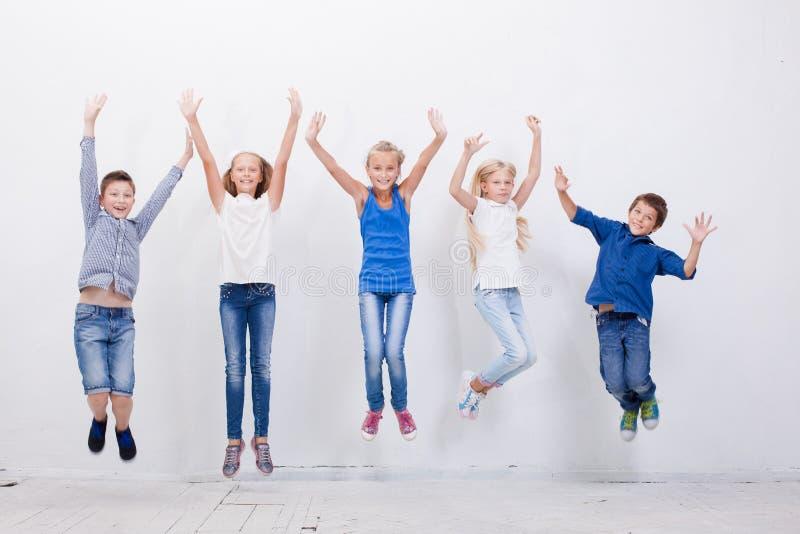 Grupo de jovens felizes que saltam no branco foto de stock