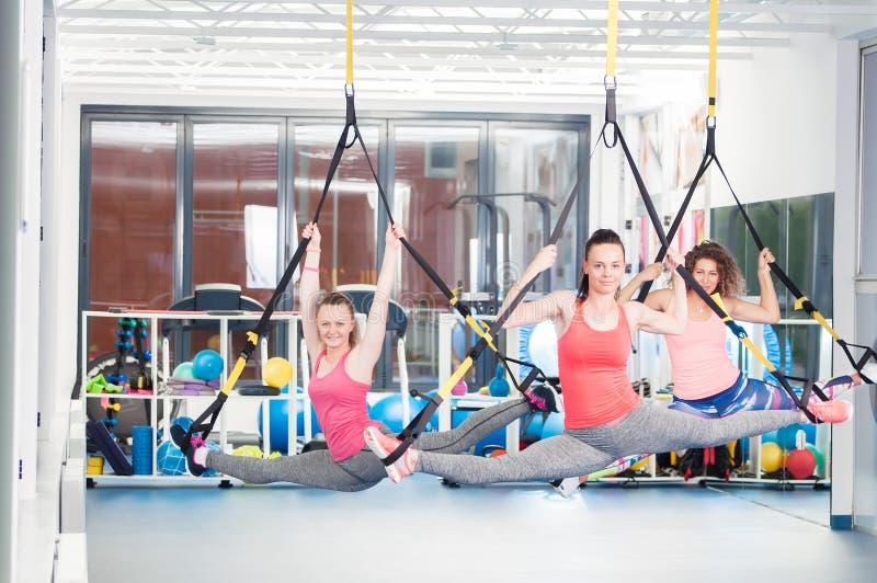 Grupo de jovens mulheres bonitas que fazem o exercício em TRX foto de stock